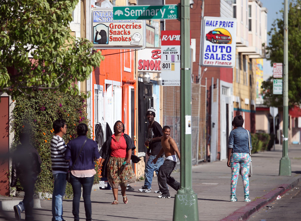 . A woman walks by youth hanging out along International Boulevard near Seminary Avenue in Oakland, Calif., on Thursday, April 18, 2013.  (Jane Tyska/Staff)