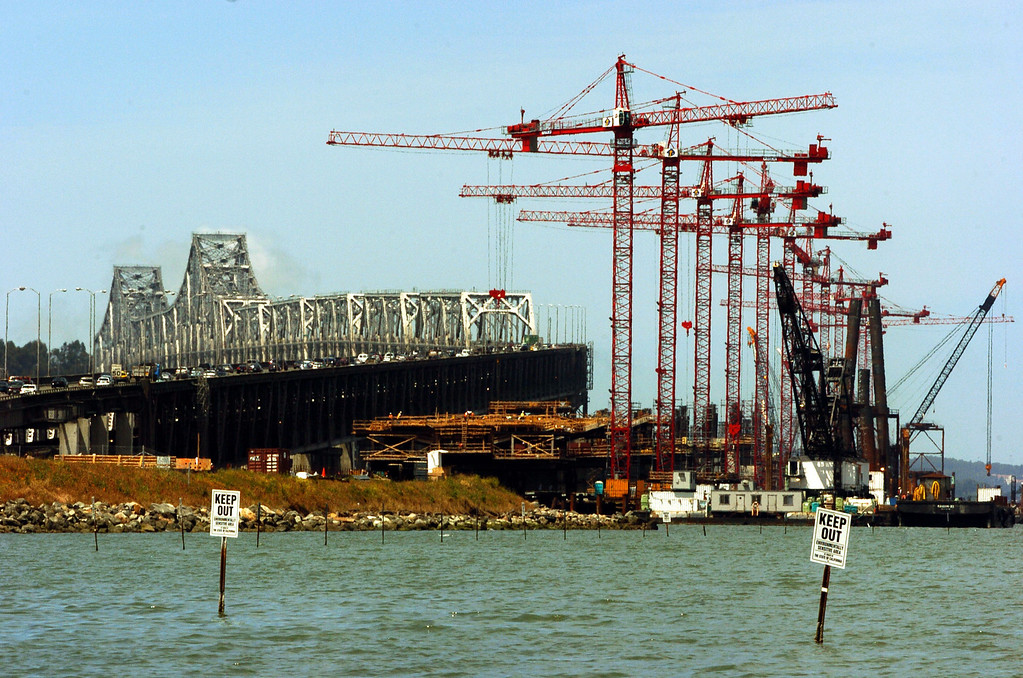 . A dozen cranes hover over the eastern span of the Oakland-San Francisco Bay Bridge construction site Tuesday morning May 18, 2004. Much of the work replacing the 68-year old eastern span is being done by the 240-foot tall cranes. (Contra Costa Times/Karl Mondon)