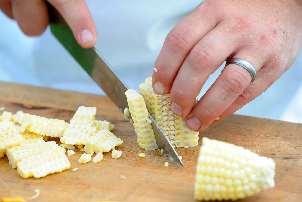 """. Matt Greco, the Chef at Livermore\'s Wente Vineyards restaurant, cuts off kernels of corn during the \""""Alameda County Mayors\' Healthy Cook-Off Challenge\"""" held at the Dublin Farmers\' Market at Emerald Glen Park in Dublin, Calif., on Thursday, July 25, 2013. The Livermore team, consisting of Greco and Livermore Mayor John Marchand, went on to take first place advancing them to compete against the winners of the Contra Cost County Mayors\' Healthy Cook-Off Challenge. The contest will be held at Mt. Diablo High School in the fall. The cook-off was presented by Concord\'s Wellness City Challenge and promotes the importance of healthy eating. (Doug Duran/Bay Area News Group)"""