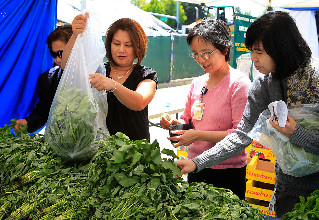 . From center left to right, shoppers Thess Tran and Dr. Lynn Giang check out the vegetables from Fresno\'s Three Brothers Farm, at the new Santa Clara Valley Medical Center Farmer\'s Market in San Jose, Calif. on Wednesday, May 15, 2013.  (LiPo Ching/Bay Area News Group)