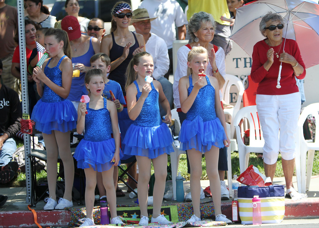 . From left, Cailey Benjamin, 11, Sydney Garcia, 7, Anna Benjamin, 9, Ashley Garcia, 11, eat ice cream while watching Redwood City\'s 75th annual Fourth of July Parade on Thursday, July 4, 2013. (Kirstina Sangsahachart/ Daily News)