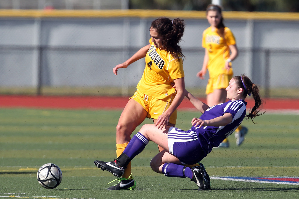 . Piedmont\'s Natalie Greening (10) slides to deflect the ball against  Bishop O\'Dowd\'s Rachel Wilson (4) in the first half of their North Coast Section Division II Girls Soccer Championship at Dublin High School soccer field in Dublin, Calif., on Saturday, Feb. 23, 2013. Bishop O\'Dowd won 3-2 in a series of penalty kicks. (Ray Chavez/Staff)