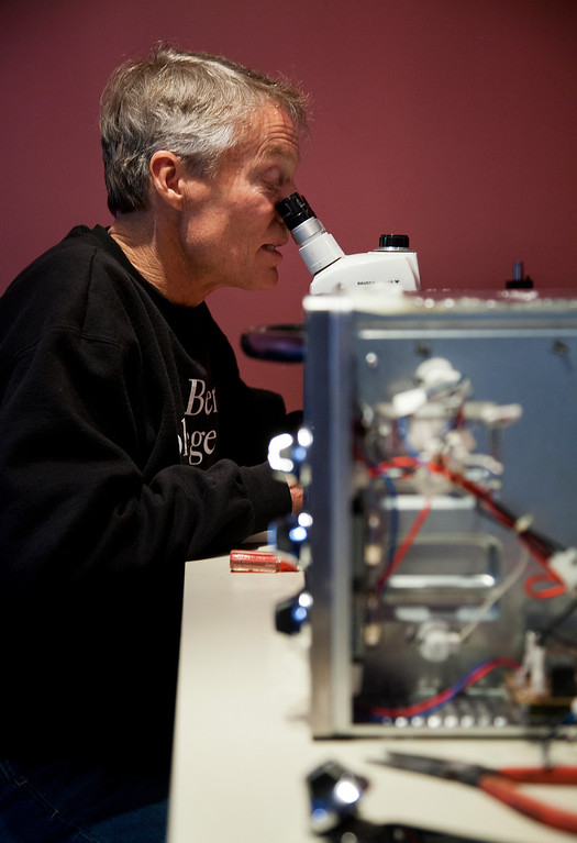 . At a microscope, John Eaton inspects the contacts of the function dial of a neighbor\'s toaster oven at his home in Palo Alto, Calif. on Friday, Feb. 15, 2013.   (LiPo Ching/Staff)