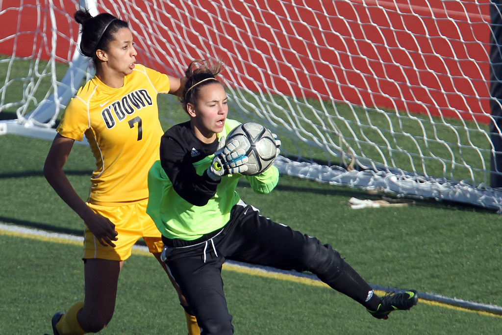 . Bishop O\'Dowd\'s Ryan Walker-Hartshorn (7) attempts a header as  Piedmont goalie Kesy Platt  controls the ball in the second half of overtime of their North Coast Section Division II Girls Soccer Championship at Dublin High School soccer field in Dublin, Calif., on Saturday, Feb. 23, 2013. Bishop O\'Dowd won 3-2 in a series of penalty kicks. (Ray Chavez/Staff)
