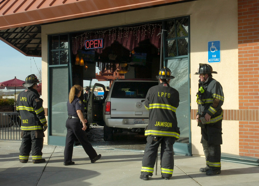 . A Cadillac Escalade SUV that was driven by accident through the Strings Italian Cafe during the lunch hour in Livermore, Calif., is prepared to be backed out by an emergency responder on Monday, Jan. 7, 2013. One customer was taken to a hospital for treatment of injuries and several other people sustained minor injuries. (Cindi Christie/Staff)