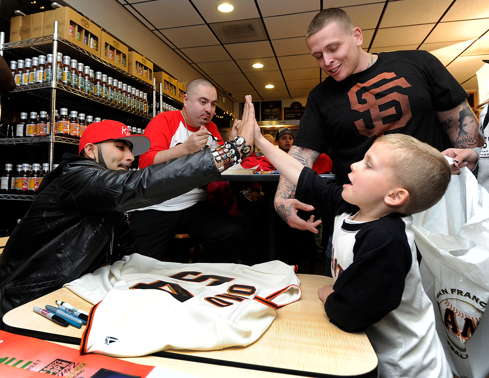 . Carlos Del Puerto, 5, of Concord gets a high-five from Giants reliever Sergio Romo as his dad Carlos Del Puerto looks on after Romo signs his dad\'s jersey at a Marine Corps Reserve Toys For Tots event on Wednesday, Dec. 12,  2012 in Pleasant Hill, Calif. Fans who brought in a toy to Kinder\'s Meats and Deli received an autograph in exchange. (Susan Tripp Pollard/Staff)
