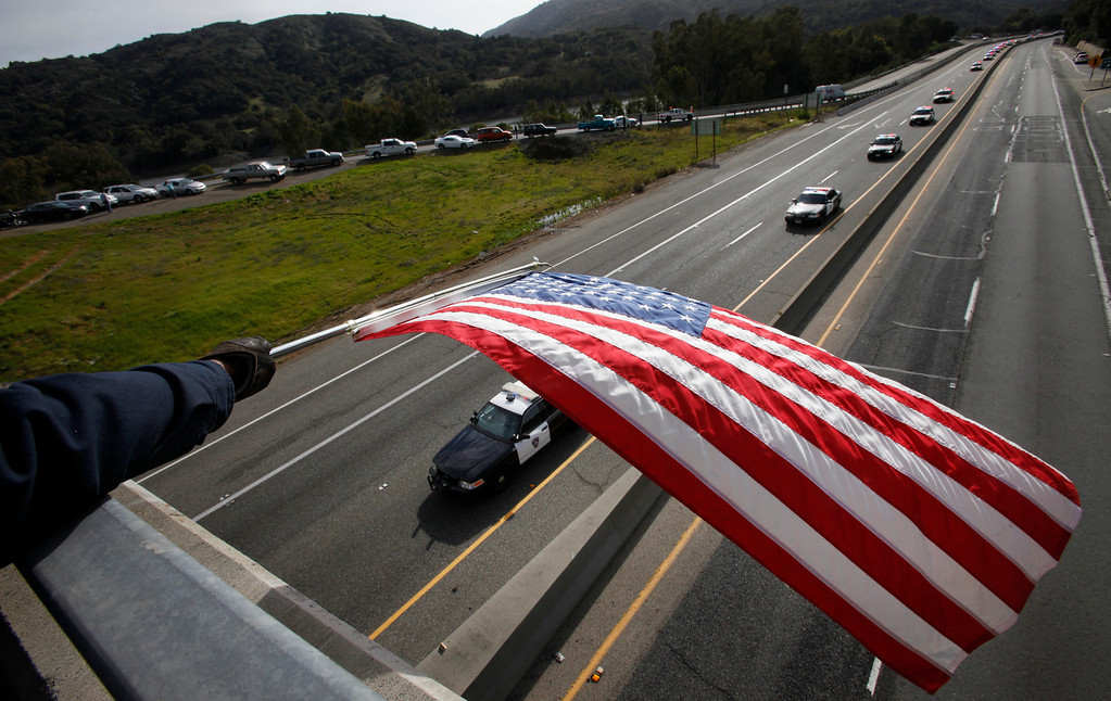 ". George Johnson, of Santa Cruz County, waves a flag as a procession of police officers from supporting agencies travel from Santa Cruz along Highway 17 near Bear Creek Road on their way to HP Pavilion in San Jose on Thursday, March 7, 2013. The procession was to the memorial service for Santa Cruz city police officers Loran ""Butch\"" Baker and Elizabeth Butler, shot to death on Feb. 26 when they followed up on a sexual assault investigation with an unstable man with a history of sexual assault. (Patrick Tehan/Bay Area News Group)"
