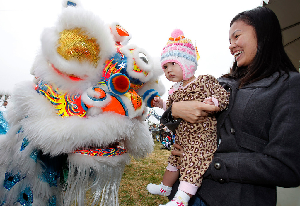 . From right, Ms. Lam and child, enjoy the Buu Kim Lion Dance Group at the Tet festival hosted by the Coalition of Nationalist Vietnamese Organizations of Northern California (CONVONCA) at the Santa Clara County Fairgrounds in San Jose, Calif. on Saturday, February 2, 2013.   (LiPo Ching/Staff)