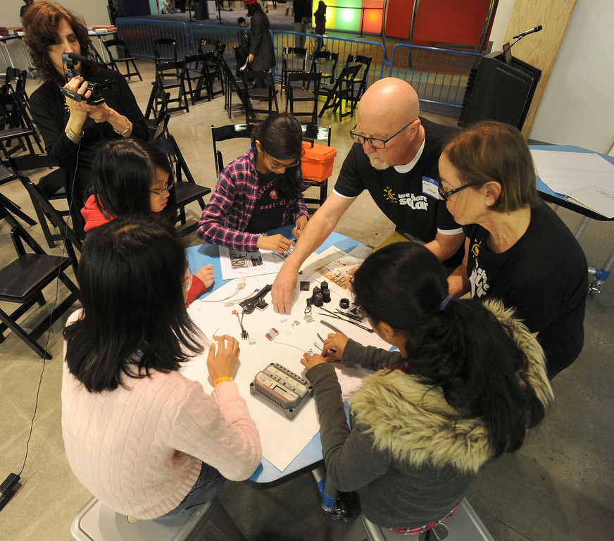 . A group of students get help laying out the parts of their solar suitcase project before assembly at the Tech Museum in San Jose, Calif., on Monday, Jan. 21, 2013. As part of Dr. Martin Luther King Jr.\'s legacy of service, young students from around the Bay Area took part in the assembling of WE CARE (Women\'s Emergency Communication and Reliable Electricity) solar suitcases. These suitcases contain a complete solar electric system that will be sent to Sierra Leone, where such kits can be life-changing, bringing light to desperately poor West African schools. The Tech Museum of Innovation is a partner in this program with WE CARE. (Dan Honda/Staff)