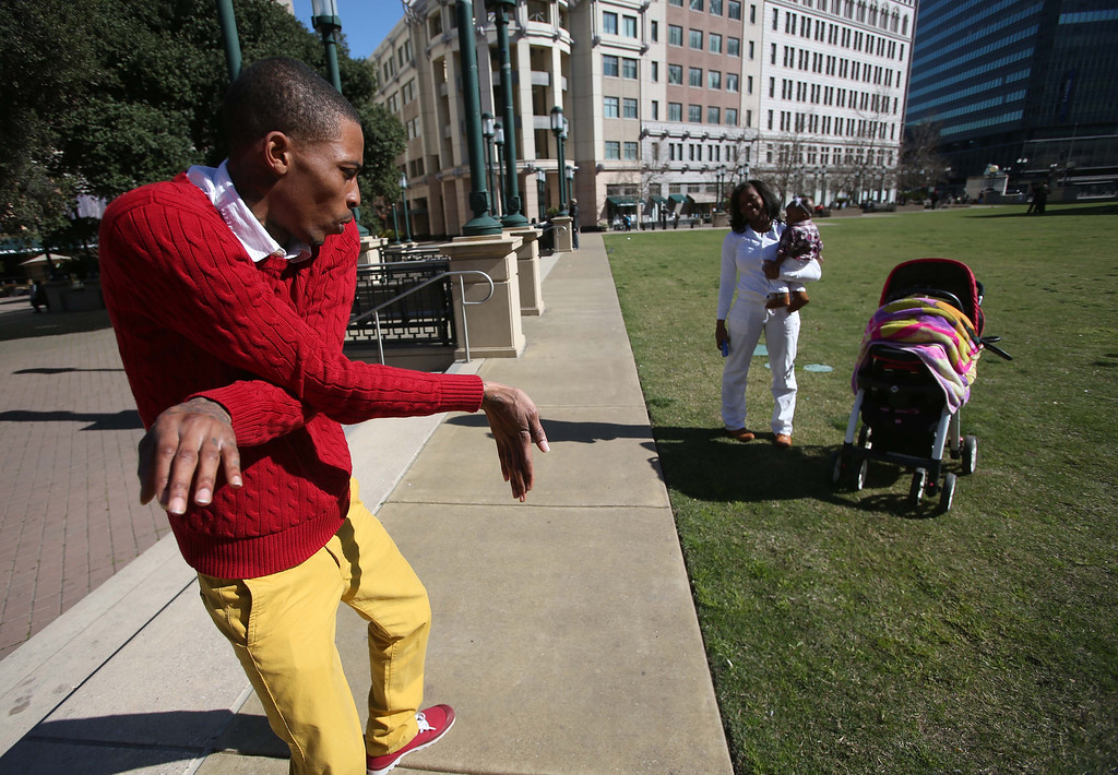 """. Darrell \""""D-Real\"""" Armstead does a turf dancing demonstration at Frank Ogawa Plaza in Oakland, Calif., on Friday, Feb. 22, 2013. To the right is his girlfriend Toni Cole and their daughter Dr\'eal Armstead, 5 months.  (Jane Tyska/Staff)"""