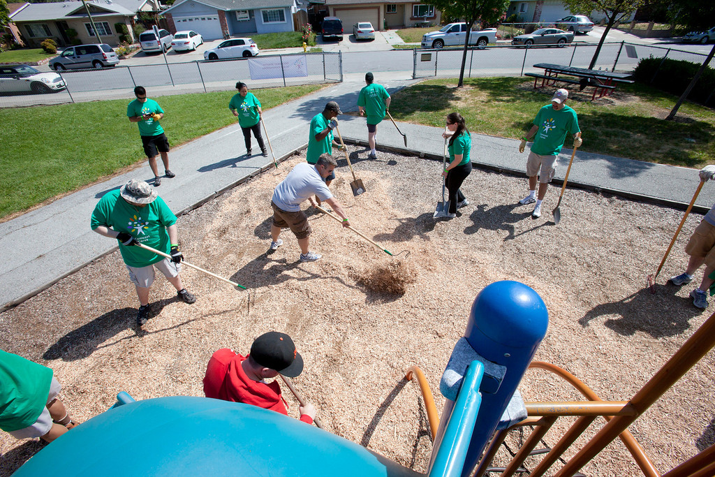 . Volunteers spread wood shavings on a play area as local Comcast employees and their families joined with students and parents to spend the morning planting, installing benches, painting, landscaping and cleaning up the grounds at Adelante Dual Language Academy in San Jose Saturday, April 27, 2013. The volunteer effort is part of the 12th �Comcast Cares Day,� the largest single-day corporate volunteer effort in the United States that brought together more than 70,000 Comcast employees, their families and friends nationwide to help make a difference in their communities.  3,000 Comcast employees and their families did volunteer work at 16 schools affected by budget cuts in California. (Patrick Tehan/Bay Area News Group)