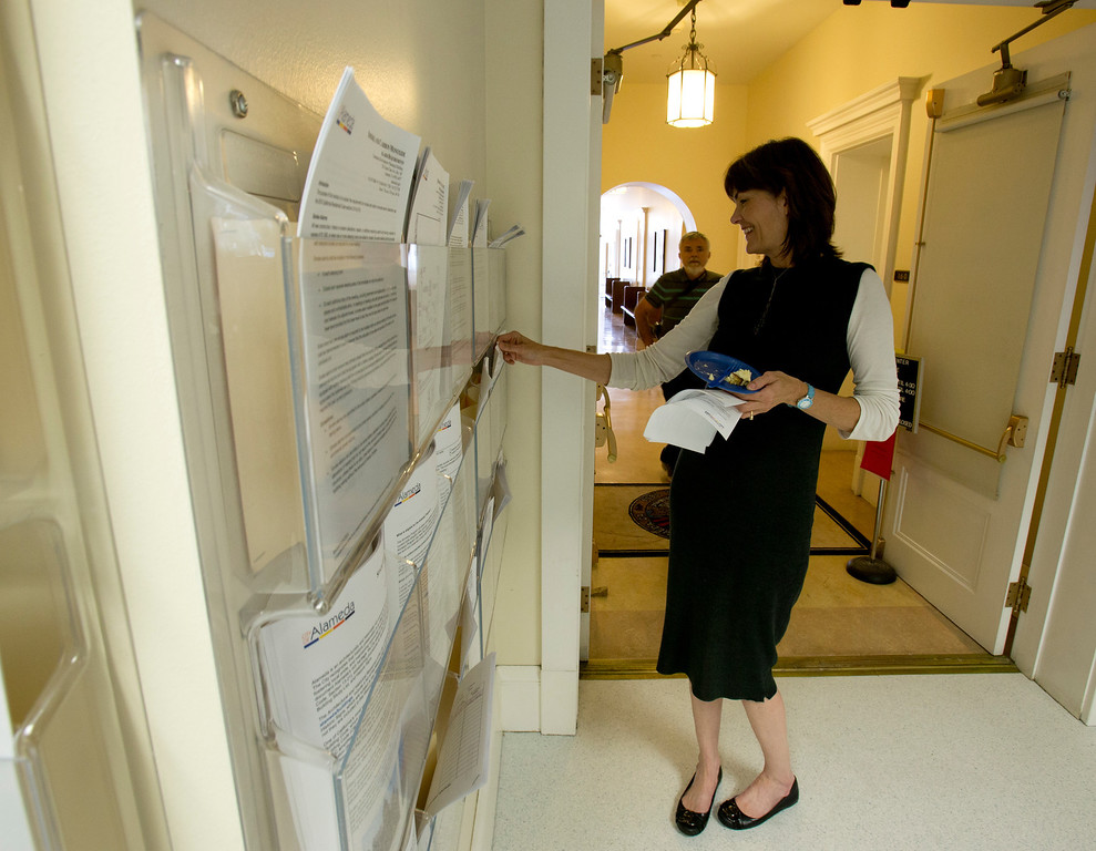 . PM Realty Group General Manager Stacey McCarthy picks out copies of permit applications at the dedication of the newly remodeled Permit Center inside City Hall, Wednesday, Nov. 6, 2013 in Alameda, Calif. (D. Ross Cameron/Bay Area News Group)