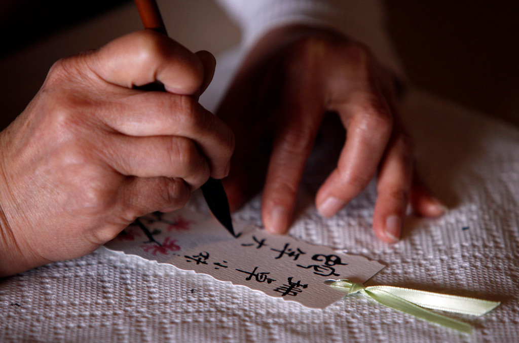 ". A calligrapher makes personalized cards for visitors at Hakone Estate and Gardens which hosted a Lunar New Year of the Snake festival with a ""Chinese Village Fair\"" on Sunday afternoon, March 3, 2013 in Saratoga, Calif. (Karl Mondon/Staff)"