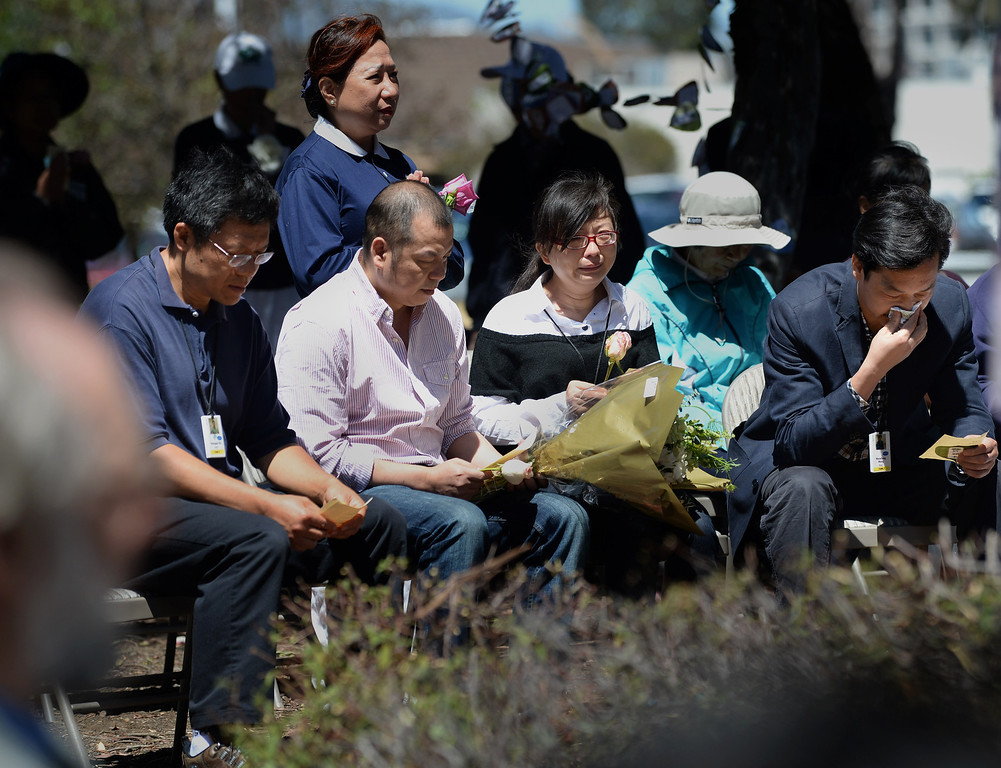 . A couple identified as the parents of Asiana crash victim Ye Mengyuan, second and third from left, and a man identified as the father of victim Wang Linjia, far right, attended a prayer ceremony for the Asiana Flight victims put on by the Tzu Chi Foundation in Burlingame, Calif., on Saturday, July 13, 2013. Tzu Chi is an international Buddhist relief organization that began in Taiwan and offers compassionate efforts for charity, medical treatment, education and disaster relief.  (Dan Honda/Bay Area News Group)
