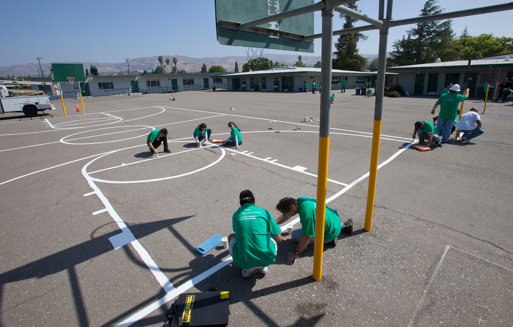 . Volunteers paint lines on a basketball court as local Comcast employees and their families joined with students and parents to spend the morning planting, installing benches, painting, landscaping and cleaning up the grounds at Adelante Dual Language Academy in San Jose Saturday, April 27, 2013. The volunteer effort is part of the 12th �Comcast Cares Day,� the largest single-day corporate volunteer effort in the United States that brought together more than 70,000 Comcast employees, their families and friends nationwide to help make a difference in their communities.  3,000 Comcast employees and their families did volunteer work at 16 schools affected by budget cuts in California. (Patrick Tehan/Bay Area News Group)
