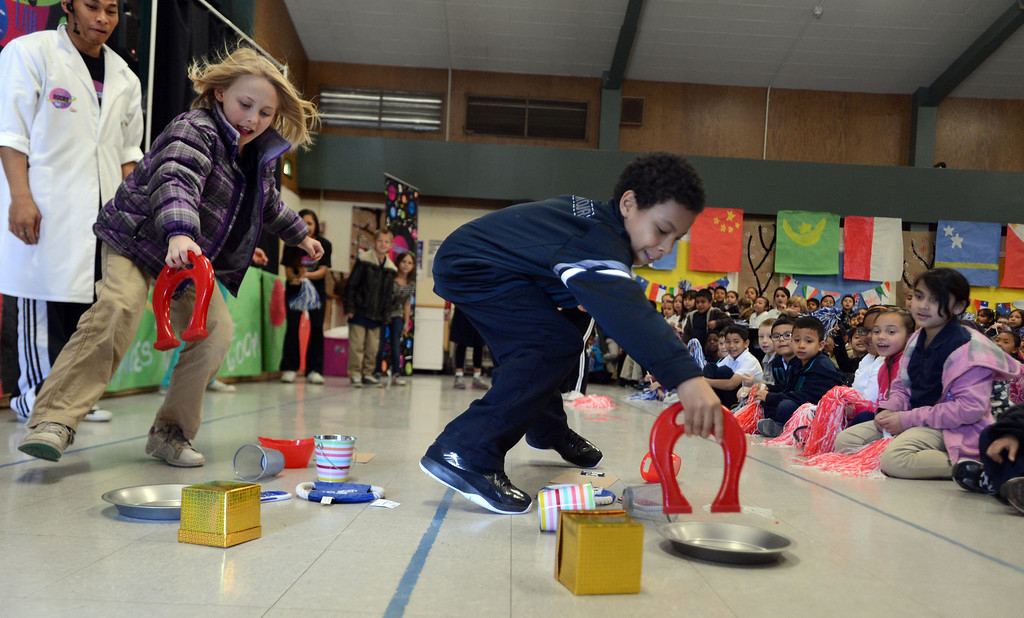 """. Third-graders Maggie Sharpe, left, and Rick Camacho race to pick up items with a magnet during a \""""Science Rocks\"""" program held at El Monte Elementary School in Concord, Calif., on Tuesday, Feb. 26, 2013.  (Susan Tripp Pollard/Staff)"""