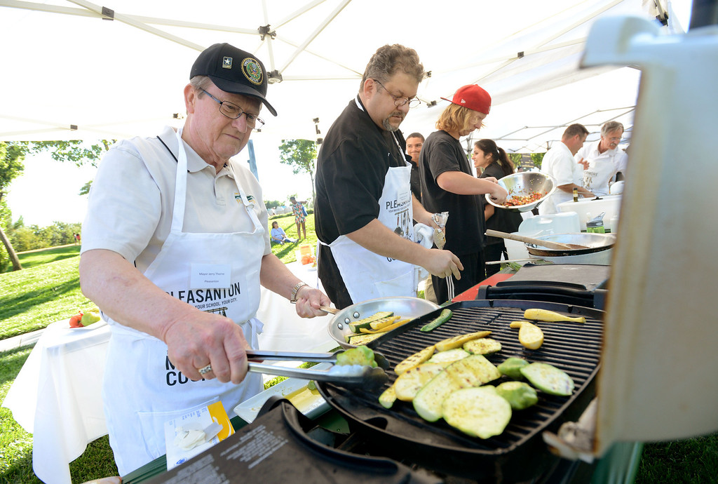 """. Pleasanton Mayor Jerry Thorne, left, and Brian Hampton, the Chef at Pleasanton\'s Handles Gastropub restaurant, get their meals ready during the \""""Alameda County Mayors\' Healthy Cook-Off Challenge\"""" held at the Dublin Farmers\' Market at Emerald Glen Park in Dublin, Calif., on Thursday, July 25, 2013. The team from Livermore went on to take first place advancing them to compete against the winners of the Contra Cost County Mayors\' Healthy Cook-Off Challenge. The contest will be held at Mt. Diablo High School in the fall. The cook-off was presented by Concord\'s Wellness City Challenge and promotes the importance of healthy eating. (Doug Duran/Bay Area News Group)"""