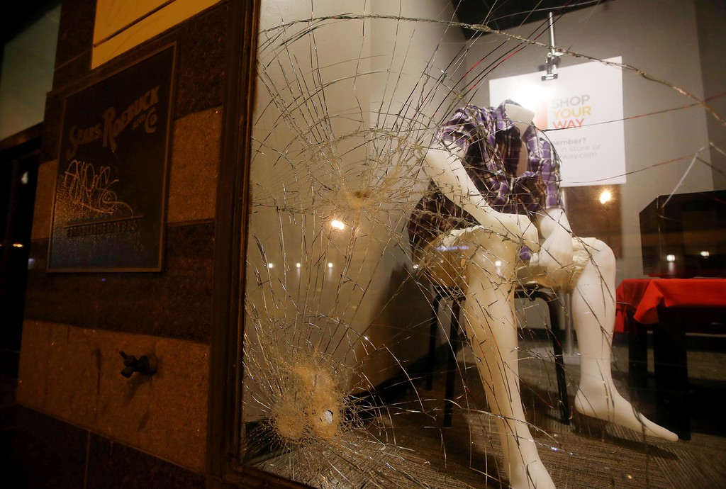 . A mannequin is seen through a smashed window at the Sears store on Telegraph Avenue near 20th Street in downtown Oakland, Calif., early Sunday, July 14, 2013. Protesters also lit several small fires on Telegraph Avenue and sprayed graffiti after learning that George Zimmerman had been found not guilty in the shooting death of Trayvon Martin in Sanford, Fla. (Jane Tyska/Bay Area News Group)