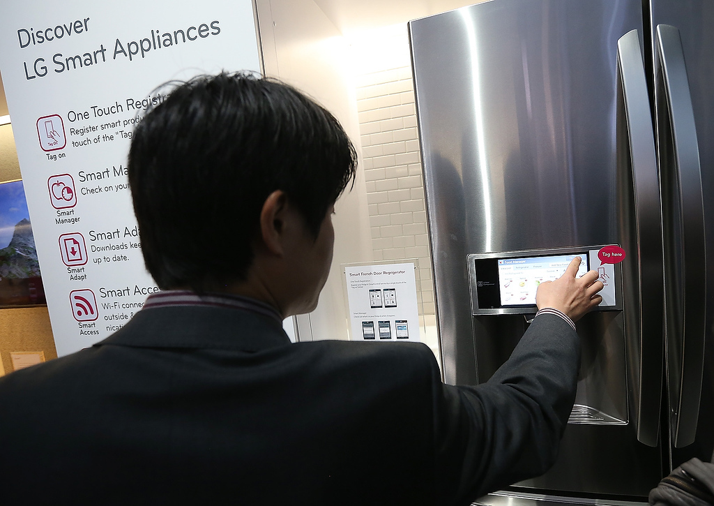. An attendee inspects an LG Smart appliance during the 2013 International CES at the Las Vegas Convention Center on January 8, 2013 in Las Vegas, Nevada. (Photo by Justin Sullivan/Getty Images)