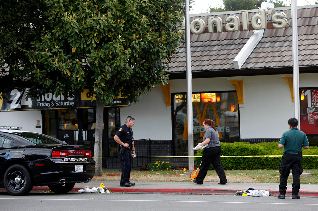 . Police investigate a crime scene where six people, including a 6-year-old child, were shot in broad daylight Sunday afternoon, May 5, 2013, on University Avenue  in East Palo Alto, Calif. (Karl Mondon/Bay Area News Group)