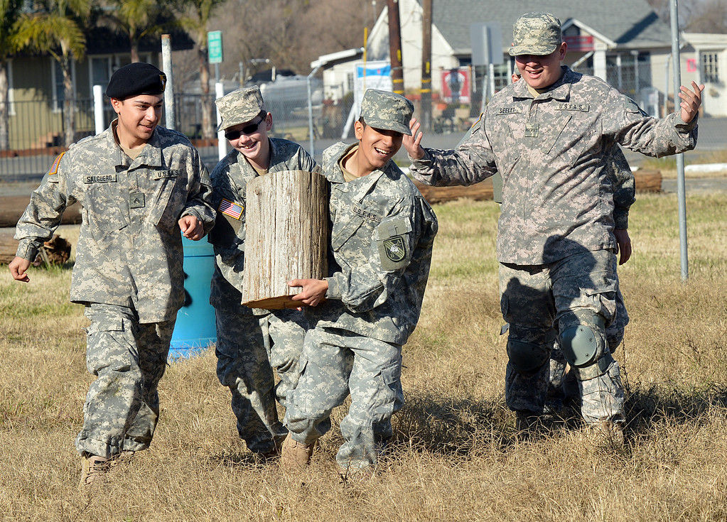. Boy Scout Javier Torres of Oakley, runs with a large piece of wood, as fellow scouts Arlen Salguero, left, of Oakley, Jonathan  Behling, center, of Brentwood, and Alton Seeley, right, of Bethel Island, run along with him during a training exercise at his battalion headquarters in Bethel Island, Calif., on Saturday Jan. 19, 2013. A group of eighteen boys are in a branch of the Boy Scouts know as Venturing. The East County club, the only Army-oriented one in northern California , not only gives kids a taste of military life but teaches them respect for authority, courtesy and self-confidence. (Dan Rosenstrauch/Staff)