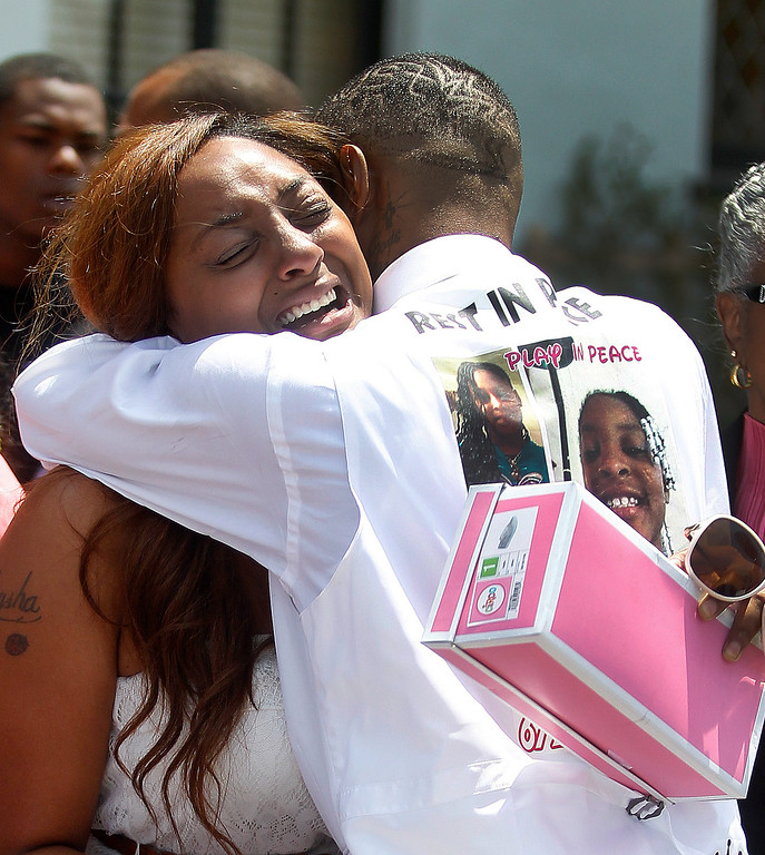 . Chiquita Carradine, left, gets a hug as she leaves McNary-Williams-Jackson Mortuary  after funeral services for her daughter Alaysha Carradine, 8, on Tuesday, July 30, 2013 in Oakland, Calif.  Alaysha Carradine was shot and killed during a sleepover at a friend\'s house in the 3400 block of Wilson Avenue earlier this month in Oakland.   (Aric Crabb/Bay Area News Group)