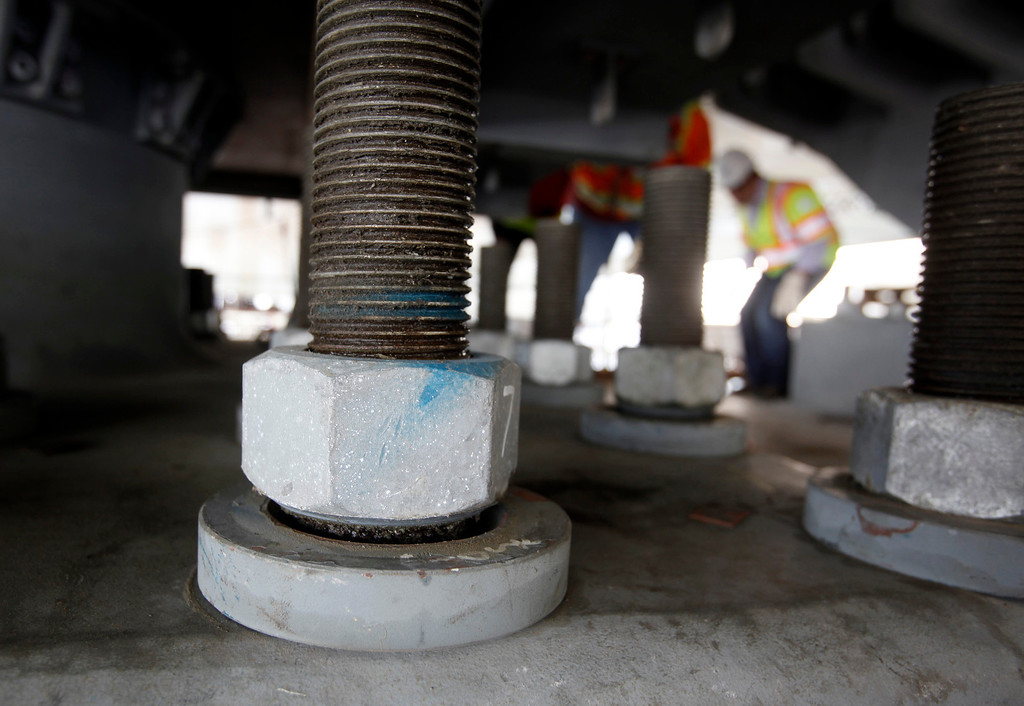. A broken anchor rod rises up next to still-tensioned rods on a shear key on the new Bay Bridge Friday afternoon May 3, 2013. Caltrans showed off the rods and some of the techniques they are using to monitor and test other installed anchor rods as they design a fix for the compromised hardware. (Karl Mondon/Bay Area News Group)