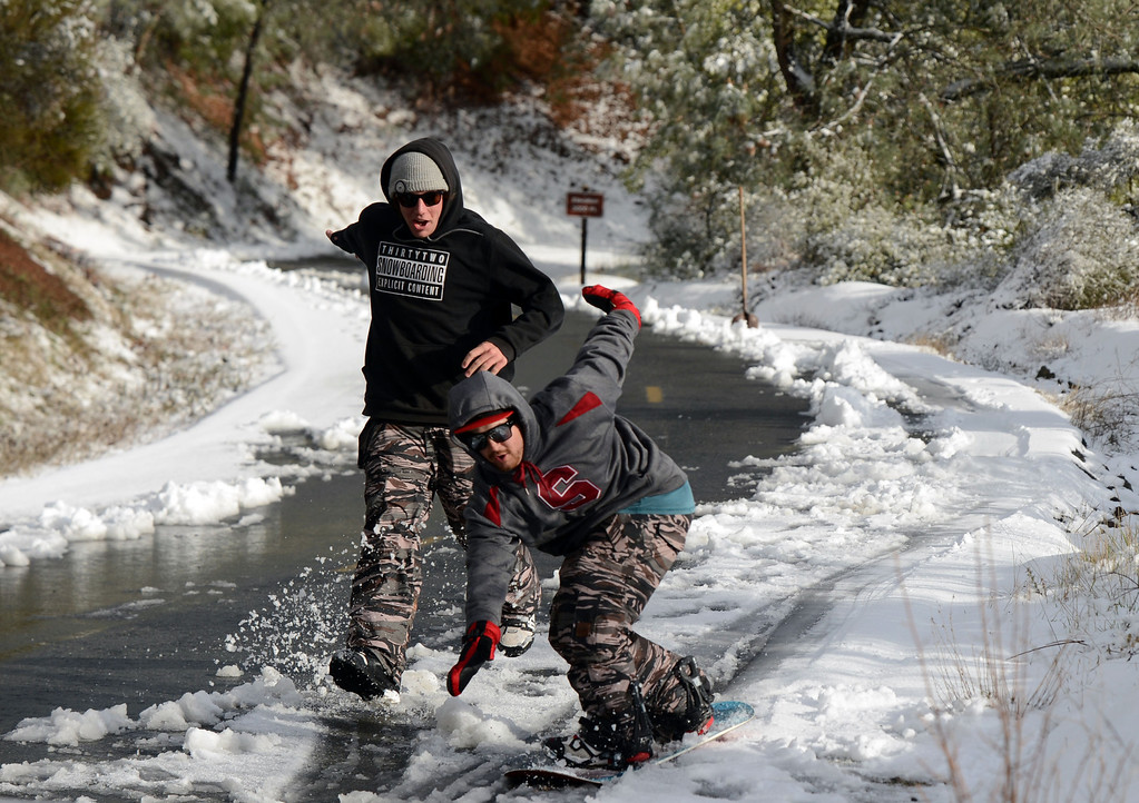 . It is a winter wonderland for Woody Wilcox, 22, of Walnut Creek, left, and Shane White, 21, of Concord, as the two take turns snowboarding down a road just shy of the 3,000 feet mark at Mount Diablo State Park in Walnut Creek, Calif., on Tuesday, Feb. 19, 2013. The two friends, who graduated from Northgate High School in 2009, took turns giving each other a push to pick up speed in the slushy snow.   (Susan Tripp Pollard/Staff)