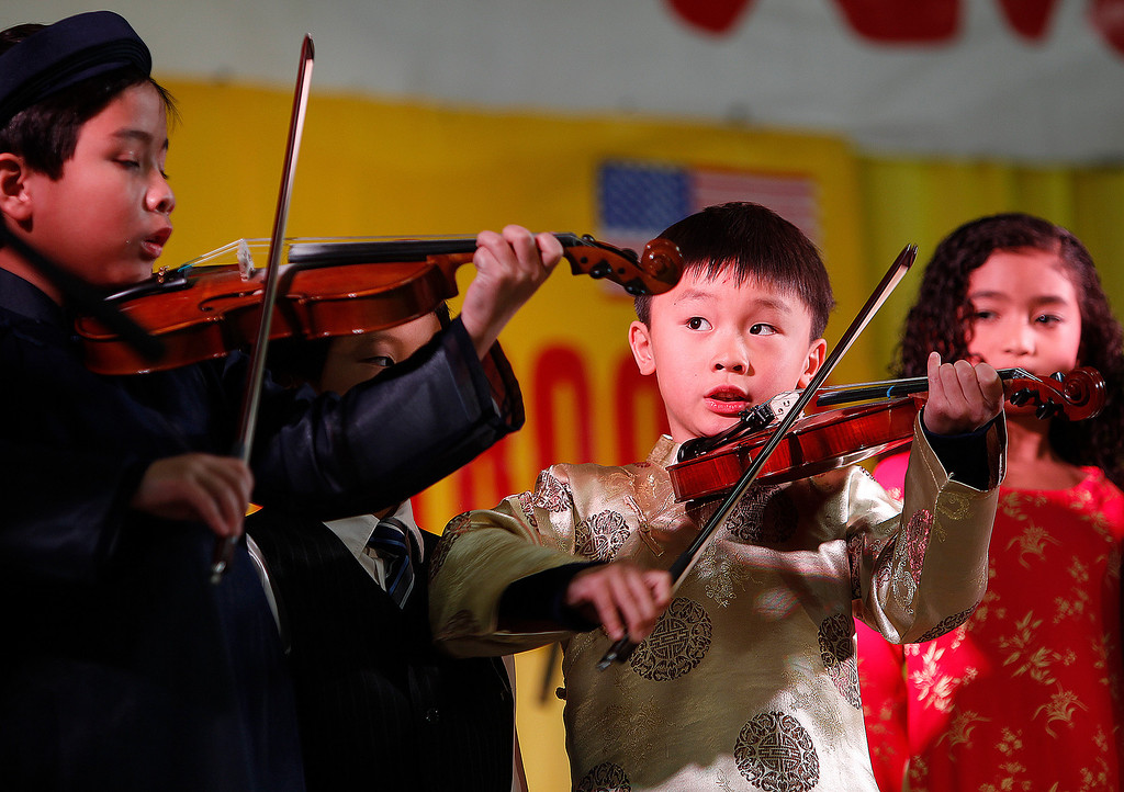 . From left, Hot Pepper musical group violinists Nathan Nguyen, 10, and Jeanhuy Nguyen, 6, perform at the Tet festival hosted by the Coalition of Nationalist Vietnamese Organizations of Northern California (CONVONCA) at the Santa Clara County Fairgrounds in San Jose, Calif. on Saturday, February 2, 2013.  The Hot Pepper musical group is part of the Pacific Music Association (PMA).   (LiPo Ching/Staff)