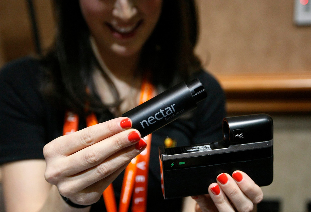 . A woman demonstrates the Nectar mobile power source at the opening press event of the Consumer Electronics Show in Las Vegas on Jan. 6, 2013. The device announced on Sunday at CES, will charge and power a mobile device for up to two weeks. (REUTERS/Rick Wilking)