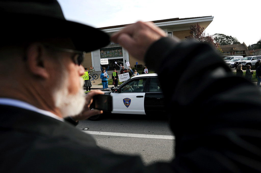 ". A man stands at attention as the funeral procession for detectives Sgt. Loran ""Butch\"" Baker and Elizabeth Butler moves down Ocean Street in Santa Cruz, Calif.,  towards Highway 17 on Thursday, March 7, 2013.  (Matthew Hintz/Santa Cruz Sentinel)"