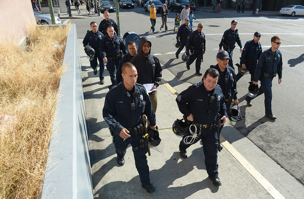 . Oakland Police in riot gear follow close behind as protesters march on Clay Street in Oakland, Calif., on Sunday, July 14, 2013. A jury ruled Saturday that defendant George Zimmerman has been found not guilty in the shooting death of Trayvon Martin. (Jose Carlos Fajardo/Bay Area News Group)
