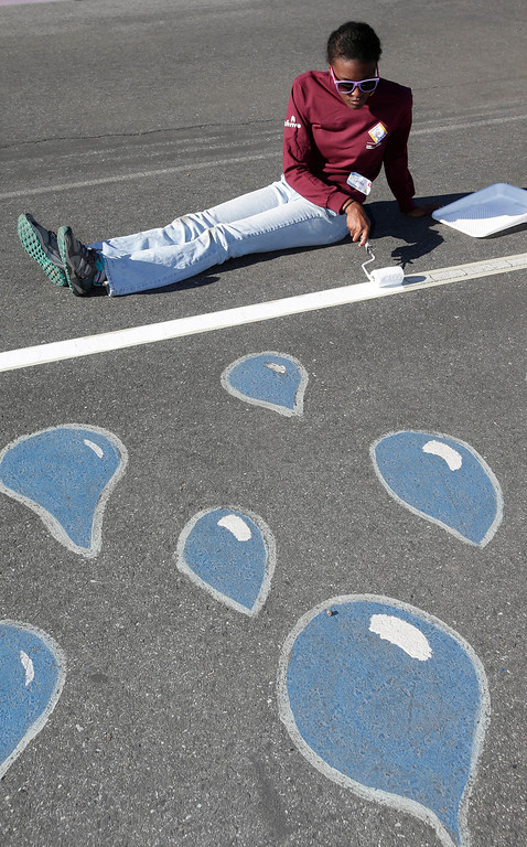 . Kaiser Permanente volunteer, Larissa Bates, repaints the play yard blacktop at Ryan Elementary School during a Dr. Martin Luther King Jr. day-of-service activity in San Jose, Calif. on Monday, January 21, 2013.  (Gary Reyes/ Staff)