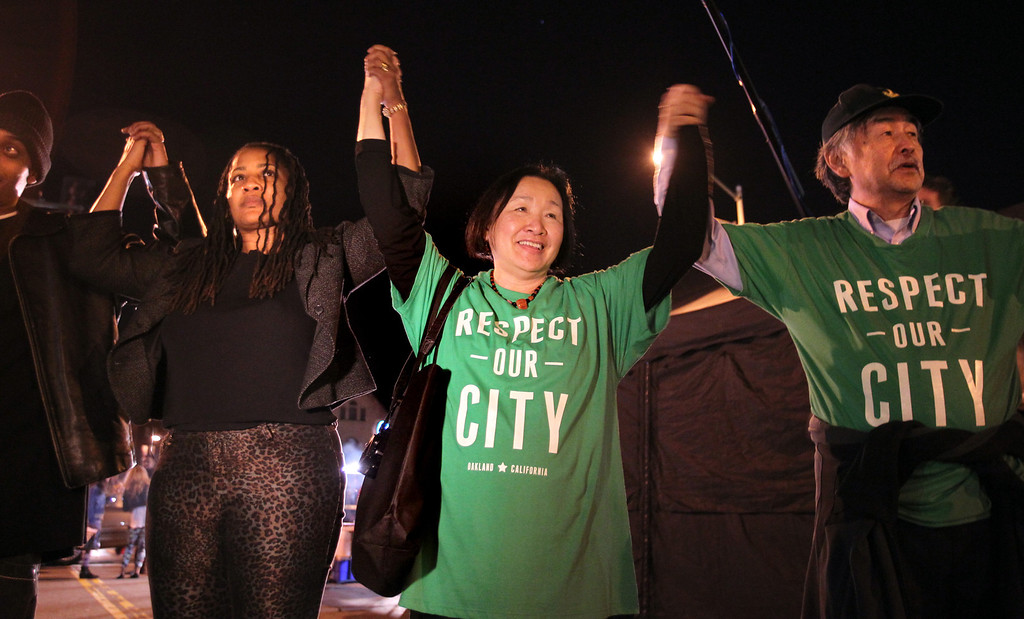 . Oakland Mayor Jean Quan, center, and her husband Floyd Huen take part in the circle of peace in honor of victims of violence at the conclusion of First Friday/Art Murmur in Oakland, Calif., on Friday, March 1, 2013. 18-year-old Kiante Campbell was shot and killed after last month\'s First Friday event in the parking lot of a beauty supply business in the 2000 block of Telegraph Avenue.  (Ray Chavez/Staff)