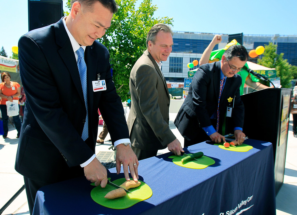 . From left, Santa Clara Valley Medical Center CEO Paul Lorenz, County Supervisor Dave Cortese, and Deputy County Executive René Santiago celebrate the opening of the new Santa Clara Valley Medical Center Farmer\'s Market with a vegetable cutting (instead of a ribbon cutting) in San Jose, Calif. on Wednesday, May 15, 2013.  (LiPo Ching/Bay Area News Group)