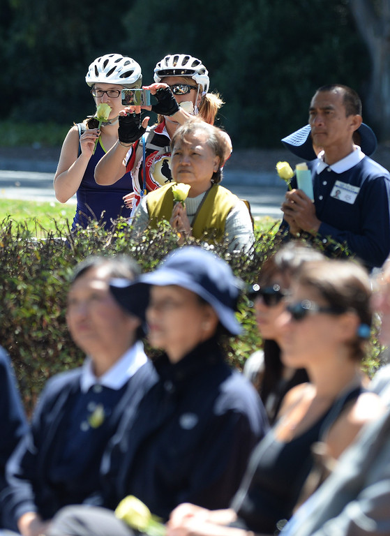 . Passersby Margaret Garziano, helmeted on right, of San Jose, and Anna Astretsova, helmeted left, of San Francisco, stop to watch a prayer ceremony for the Asiana Flight victims put on by the Tzu Chi Foundation in Burlingame, Calif., on Saturday, July 13, 2013. Tzu Chi is an international Buddhist relief organization that began in Taiwan and offers compassionate efforts for charity, medical treatment, education and disaster relief.  (Dan Honda/Bay Area News Group)