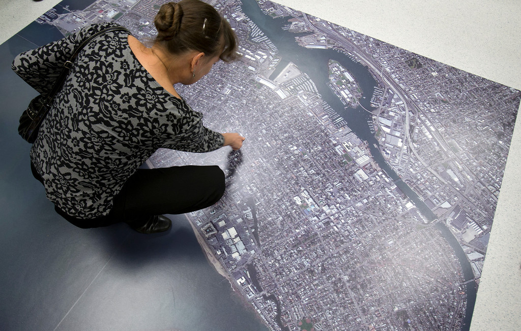 . Denise Brady of Alameda, Calif. points to her home on the aerial photo of the city, at the newly remodeled Permit Center inside City Hall, Wednesday, Nov. 6, 2013 in Alameda. (D. Ross Cameron/Bay Area News Group)