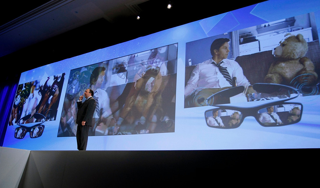 . Joe Stinziano, executive vice-president for Samsung Electronics America, demonstrates a new television that shows two programs at once at the Samsung news conference at the Consumer Electronics Show (CES) in Las Vegas January 7, 2013. Two people can watch two programs on the same TV using special glasses (seen at right). (REUTERS/Rick Wilking)