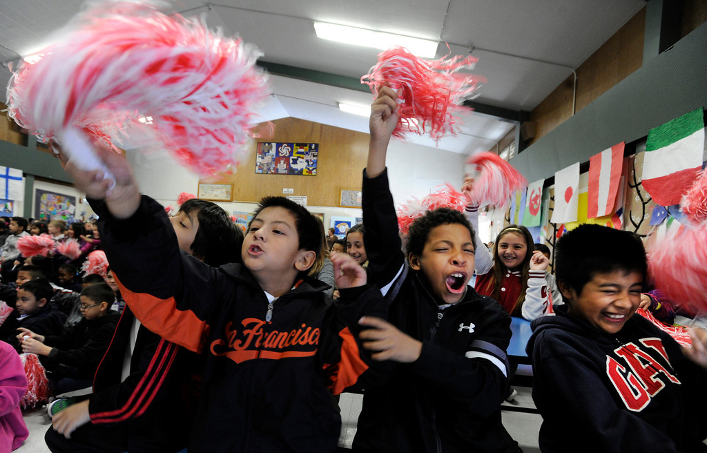 """. Demonstrating their human motion energy and their ability to make wind, third-graders from left, Gabriel David, Rick Camacho and Joseph Juarez Aguilar jump up and down and wave their pom poms for the red team during a \""""Science Rocks\"""" program at El Monte Elementary School in Concord, Calif., on Tuesday, Feb. 26, 2013. (Susan Tripp Pollard/Staff)"""