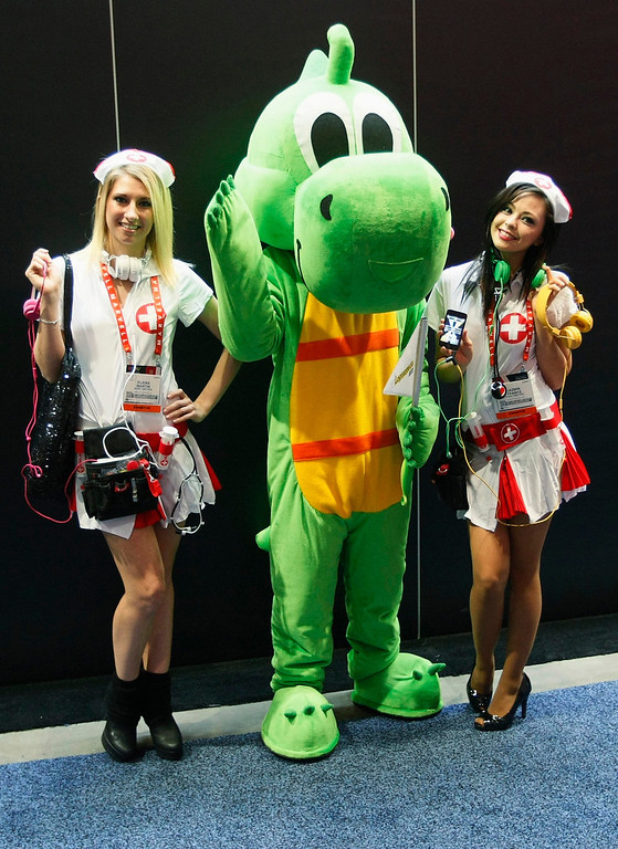 . Women dressed as nurses promoting the Headquake sound app pose with Dino the dinosaur promoting the Logistopedia logistics company on the first day of the Consumer Electronics Show (CES) in Las Vegas January 8, 2013. (REUTERS/Rick Wilking)