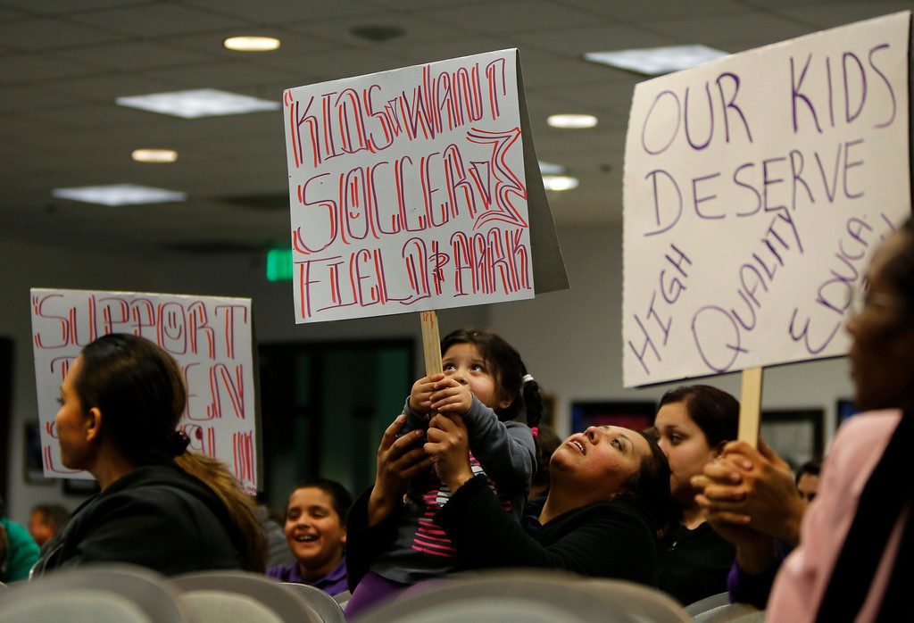 . Elena Vasquez holds her 3 year-old daughter Metzli while they hold a sign in support of Rocketship Education\'s petition to build a new school during the Santa Clara County Board of Education meeting at the Santa Clara County Office of Education San Jose, Calif. on Wednesday, Jan. 23, 2013.  (Nhat V. Meyer/Staff)