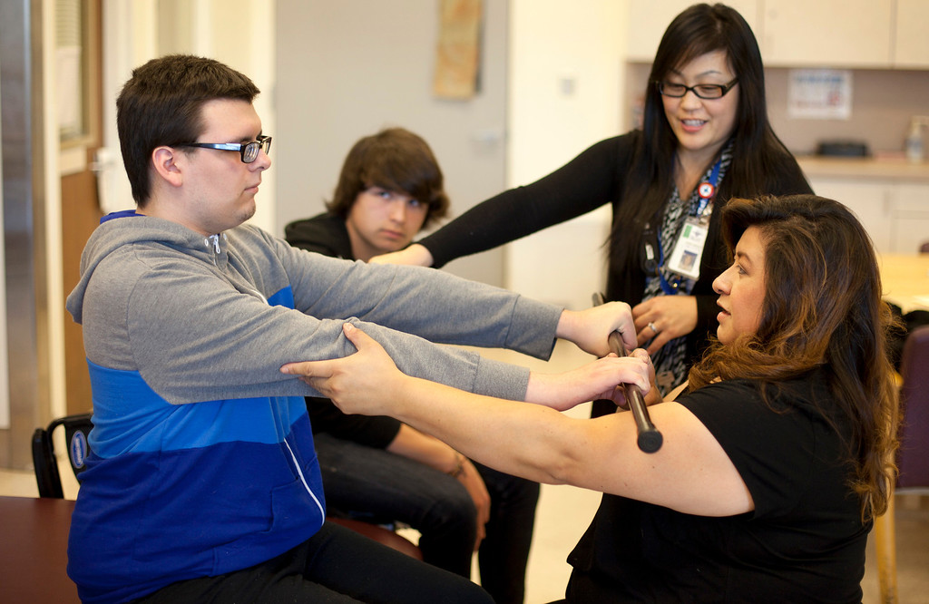 . Therapist Annie Orozco, top right, shows Delva Zamarron how to work with her son, Everett, as his brother, Coady, 13, looks on while Everett undergoes physical therapy at the Valley Medical Center rehabilitation center in San Jose Thursday, Jan. 3, 2013. (Patrick Tehan/Staff)