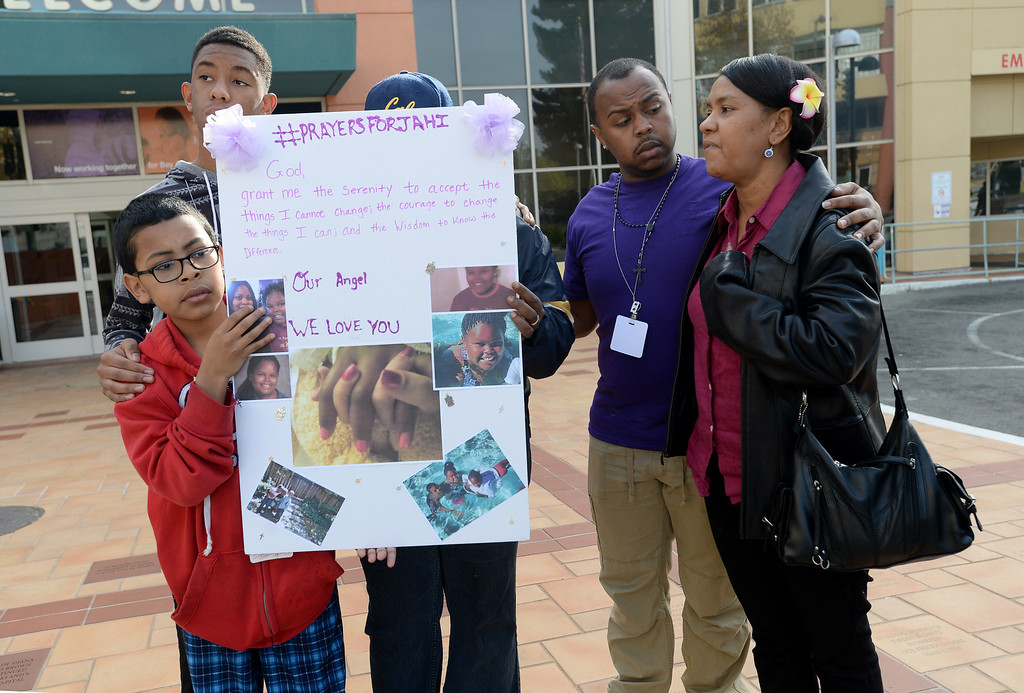 . From right, Betty Chatman, great aunt, Donn Desboine, cousin, Isaiah Chatman, cousin, and Jose Llamas, 10, brother, far left, ask for prayers for their loved one Jahi McMath in front of Oakland\'s Children\'s Hospital in Oakland, Calif., on Tuesday, Dec. 17, 2013. McMath, 13,  is fighting for her life following complications from a emove her tonsils and clear tissue from her nose and throat to treat her sleep apnea and other health issues. The person behind the sign is unidentified.(Dan Honda/Bay Area News Group)