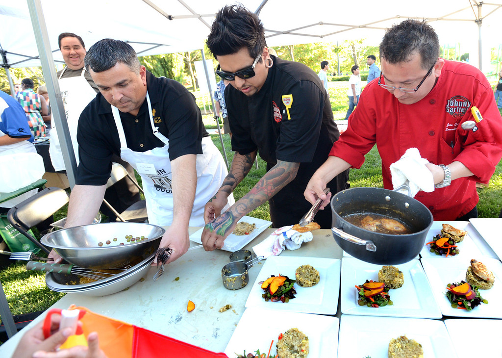 """. From left, Dublin Mayor Tim Sbranti, Ulises Rodriguez, the Sous-chef at Johnny Garlic\'s restaurant and Jose Guevara, the Chef at Johnny Garlic\'s restaurant, prepare their plates of food in the final minutes of the \""""Alameda County Mayors\' Healthy Cook-Off Challenge\"""" held at the Dublin Farmers\' Market at Emerald Glen Park in Dublin, Calif., on Thursday, July 25, 2013. The Dublin team went on to take second place advancing them to compete against the winners of the Contra Cost County Mayors\' Healthy Cook-Off Challenge. The contest will be held at Mt. Diablo High School in the fall. The cook-off was presented by Concord\'s Wellness City Challenge and promotes the importance of healthy eating. (Doug Duran/Bay Area News Group)"""