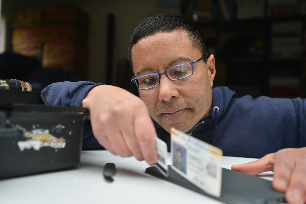 """. Using credit cards and an old driver\'s license, Peter Mui opens the plastic case of a Kindle at his home in Berkeley, Calif. on Tuesday, Feb. 5, 2013. Mui learned that the Kindle has a malfunctioning battery and might be repairable. Mui and others run \""""Fixit Clinics,\"""" where they assist people in the repair of various electrical appliances, from televisions to toasters. (Kristopher Skinner/Staff)"""