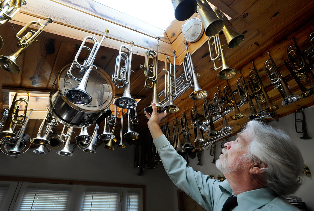 . Frank Dorritie hangs up one of his bugles in his home studio collection of about 200 bugles on Thursday, May 23, 2013, in East Contra Costa County, Calif. (Susan Tripp Pollard/Bay Area News Group)