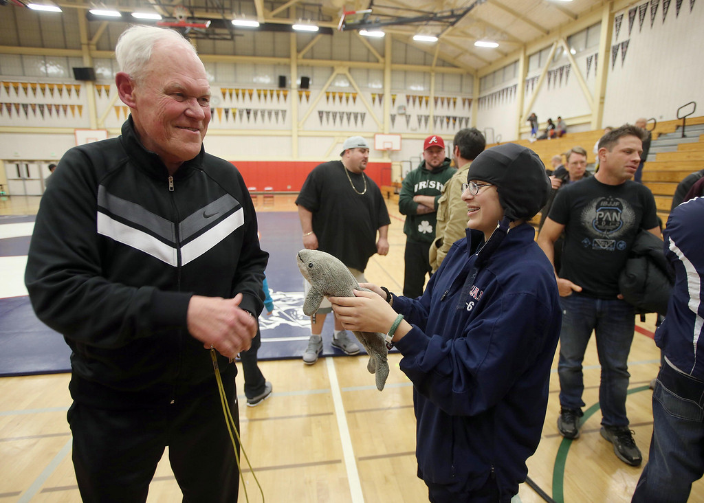 ". Albany High School wrestling coach Kermit Bankson, left, talks with wrestler Anastasia Malanche, 15, as she shows him her dolphin mascot named ""April\"" after their match against Tennyson High School in Albany, Calif. on Friday, Jan. 17, 2013. (Jane Tyska/Staff)"