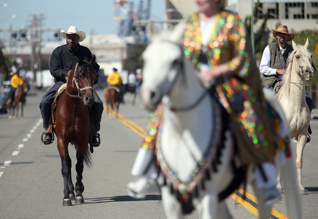 . Black cowboys and one lone white cowgirl ride down 18th Street near De Fremery Park during the 39th annual Oakland Black Cowboy Parade and Heritage Festival in Oakland, Calif., on Saturday, Oct. 5, 2013. The event also featured food, entertainment and pony rides for kids. The Oakland Black Cowboy Association began in 1975 and educates the public about the role that black cowboys played in history and building of the west. (Jane Tyska//Bay Area News Group)