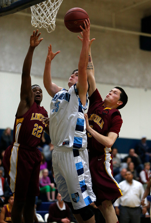. Bellarmine College Preparatory\'s Eric Straka (35) takes a shot against Lincoln High School\'s Davion Telfor (22) and Lincoln High School\'s James Gurr (5) for their NorCal Division I Round 1 game in the first period at Bellarmine College Preparatory in San Jose, Calif., on Wednesday, March 6, 2013.  (Nhat V. Meyer/Staff)