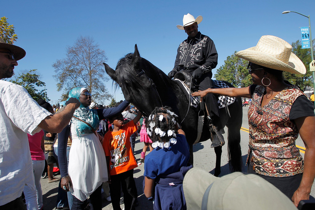 . Keith Shanks, of Oakland, and his horse Black Beauty make are greeted by the crowd during the 39th annual Oakland Black Cowboy Parade and Heritage Festival in Oakland, Calif., on Saturday, Oct. 5, 2013. The event also featured food, entertainment and pony rides for kids at De Fremery Park. The Oakland Black Cowboy Association began in 1975 and educates the public about the role that black cowboys played in history and building of the west. (Jane Tyska//Bay Area News Group)